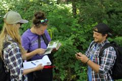 Chrissy Schellenberg and Haley Tomlin identify a plant while Alex Harte tries to find where they are on the map app.